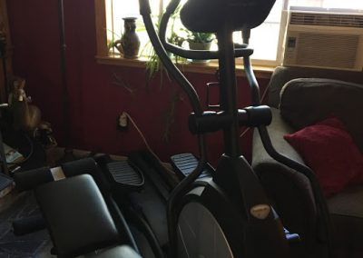 Exercise equipment (elliptical and situp bench) in the shared space.
